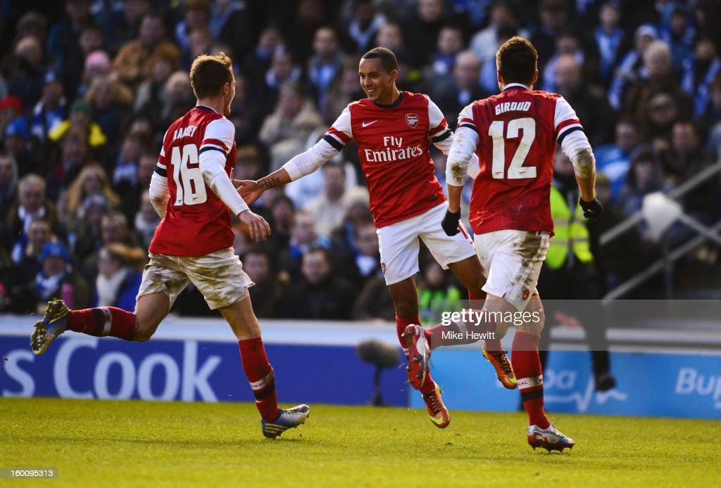 Theo Walcott of Arsenal (C) celebrates with Aaron Ramsey (16) and Olivier Giroud (12) as her scores their third goal during the FA Cup with Budweiser Fourth Round match between Brighton & Hove Albion and Arsenal at Amex Stadium on January 26, 2013 in Brighton, England.
