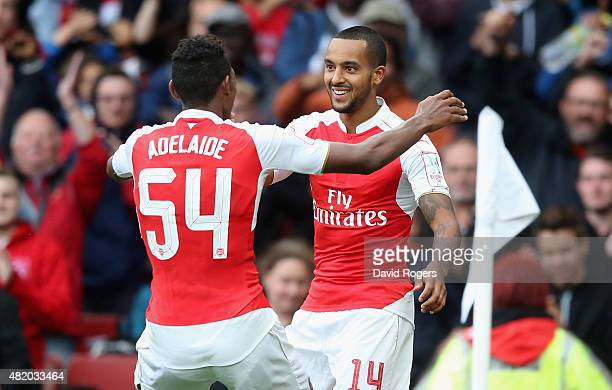 Theo Walcott of Arsenal celebrates with team mate Jeff ReineAdelaide during the Emirates Cup match between Arsenal and VfL Wolfsburg at the Emirates...