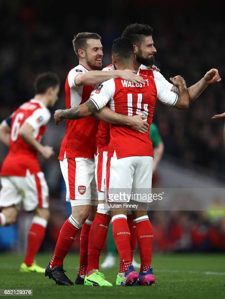 Theo Walcott of Arsenal celebrates with team mates as he scores the first goal during The Emirates FA Cup QuarterFinal match between Arsenal and...