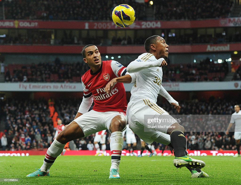 <a gi-track='captionPersonalityLinkClicked' href=/galleries/search?phrase=Theo+Walcott&family=editorial&specificpeople=451535 ng-click='$event.stopPropagation()'>Theo Walcott</a> of Arsenal challenged by Jonathan De Guzman of Swansea during the Barclays Premier League match between Arsenal and Swansea City, at Emirates Stadium on December 01, 2012 in London, England.
