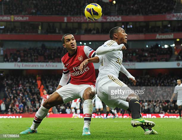 Theo Walcott of Arsenal challenged by Jonathan De Guzman of Swansea during the Barclays Premier League match between Arsenal and Swansea City at...