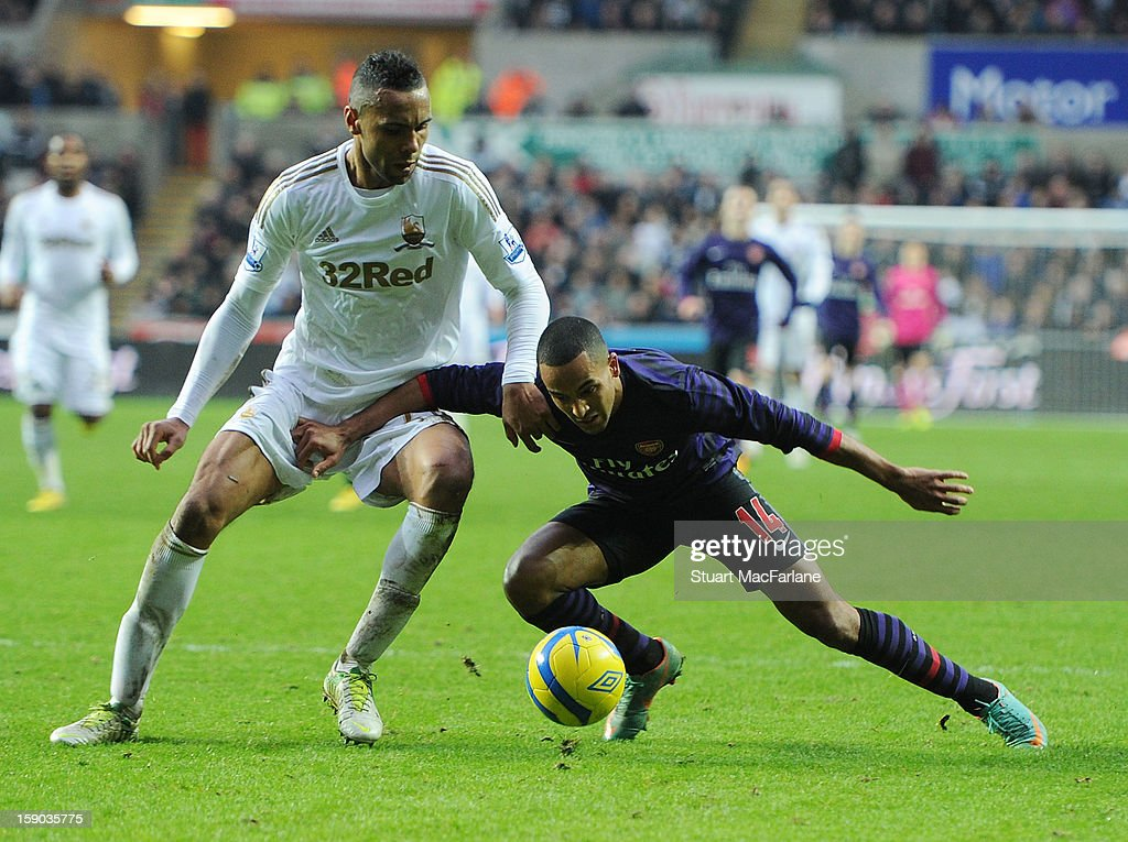 <a gi-track='captionPersonalityLinkClicked' href=/galleries/search?phrase=Theo+Walcott&family=editorial&specificpeople=451535 ng-click='$event.stopPropagation()'>Theo Walcott</a> of Arsenal challenged by Kyle Bartley of Swansea during the FA Cup Third Round match between Swansea City and Arsenal at the Liberty Stadium on January 6, 2013 in Swansea, Wales.