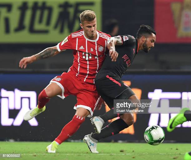 Theo Walcott of Arsenal challenged by Niklas Dorsch of Bayern Munich during a pre season friendly between Bayern Munich and Arsenal at Shanghai...