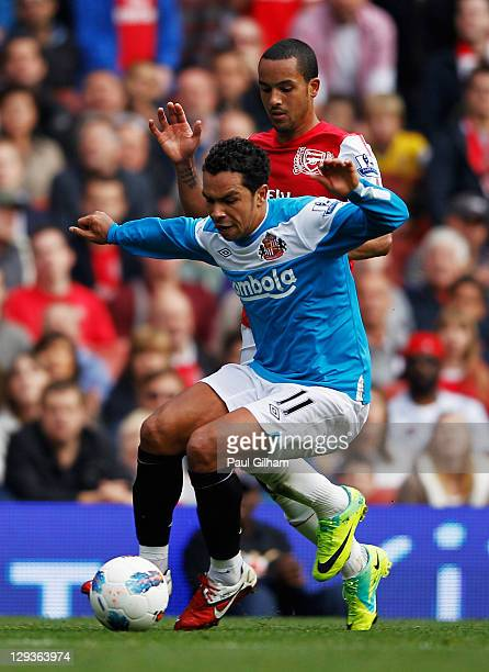 Theo Walcott of Arsenal challenges Kieran Richardson of Sunderland during the Barclays Premier League match between Arsenal and Sunderland at the...