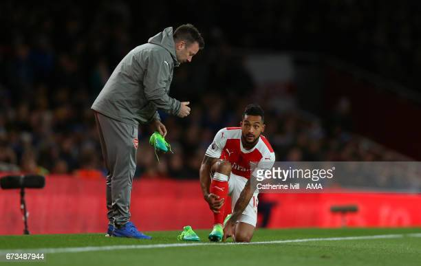Theo Walcott of Arsenal changes his boots during the Premier League match between Arsenal and Leicester City at Emirates Stadium on April 26 2017 in...