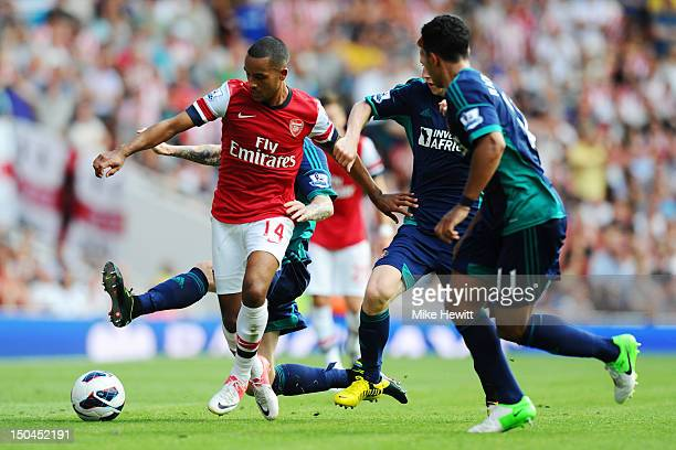 Theo Walcott of Arsenal competes for the ball against Jack Colback and Kieran Richardson of Sunderland during the Barclays Premier League match...