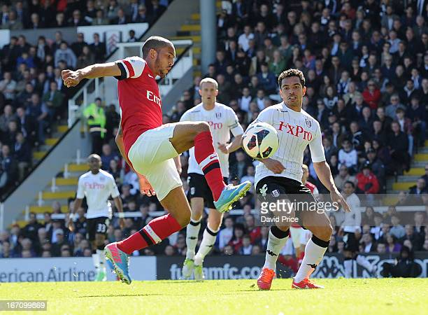 Theo Walcott of Arsenal controls the ball under pressure from Kieran Richardson of Fulham during the Barclays Premier League match between Fulham and...