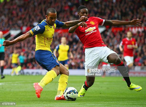 Theo Walcott of Arsenal crosses the ball which deflects of off Tyler Blackett of Manchester United for an own goal during the Barclays Premier League...