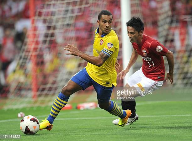 Theo Walcott of Arsenal FC shields the ball from Kunimitsu Sekiguchi of Uwawa during the preseason Asian Tour friendly match between Urawa Red...