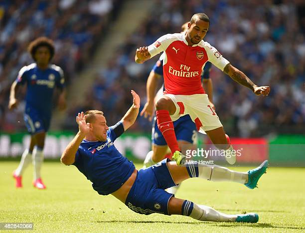 Theo Walcott of Arsenal hurdles a challenge from John Terry of Chelsea during the FA Community Shield match between Chelsea and Arsenal at Wembley...