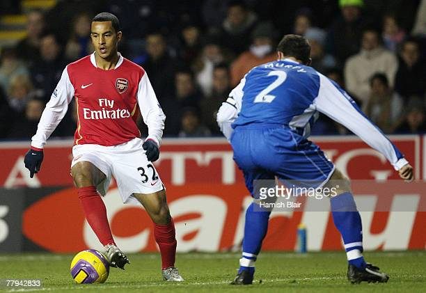 Theo Walcott of Arsenal in action with Graeme Murty of Reading looking on during the Barclays Premier League match between Reading and Arsenal at...