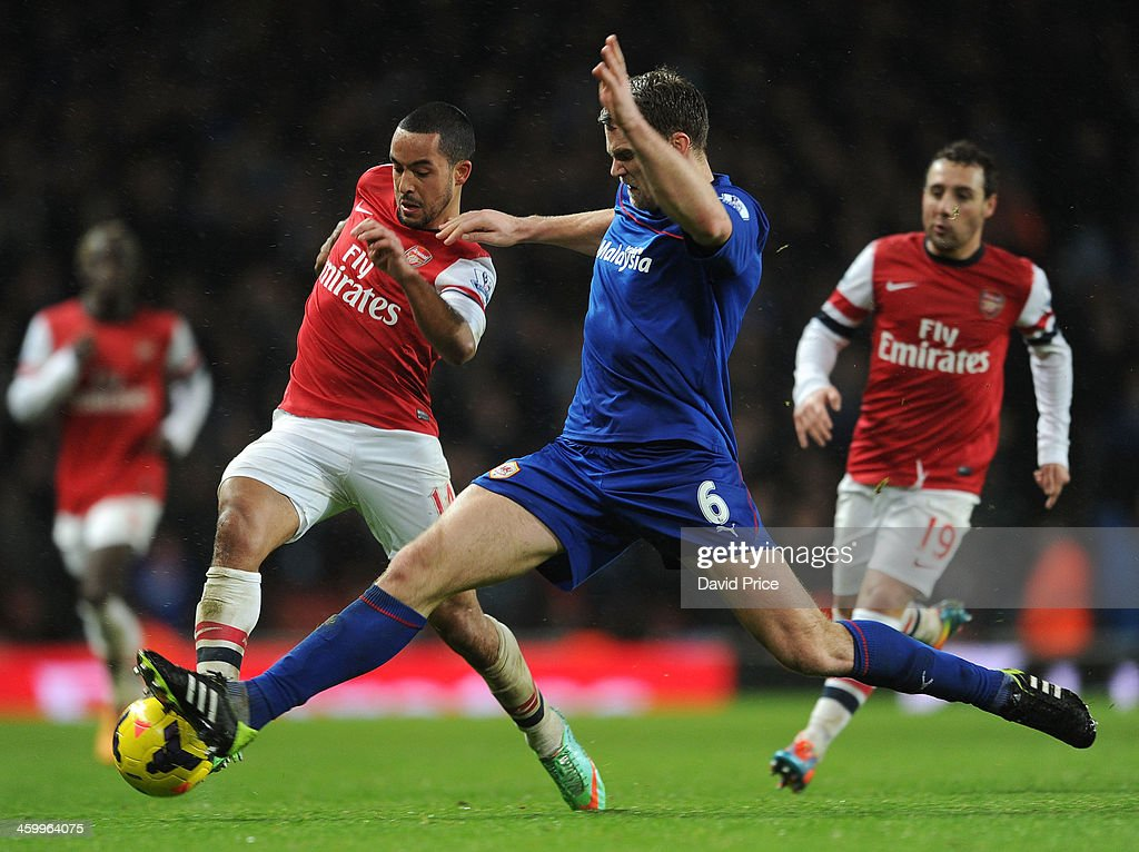 Theo Walcott of Arsenal is challenged by Ben Turner of Cardiff during the match Arsenal against Cardiff City in the Barclays Premier League at Emirates Stadium on January 1, 2014 in London, England.