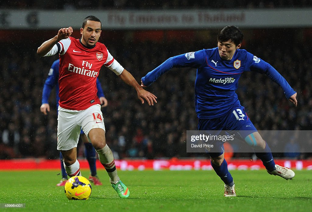 <a gi-track='captionPersonalityLinkClicked' href=/galleries/search?phrase=Theo+Walcott&family=editorial&specificpeople=451535 ng-click='$event.stopPropagation()'>Theo Walcott</a> of Arsenal is challenged by <a gi-track='captionPersonalityLinkClicked' href=/galleries/search?phrase=Kim+Bo-Kyung&family=editorial&specificpeople=6963360 ng-click='$event.stopPropagation()'>Kim Bo-Kyung</a> of Cardiff during the match Arsenal against Cardiff City in the Barclays Premier League at Emirates Stadium on January 1, 2014 in London, England.