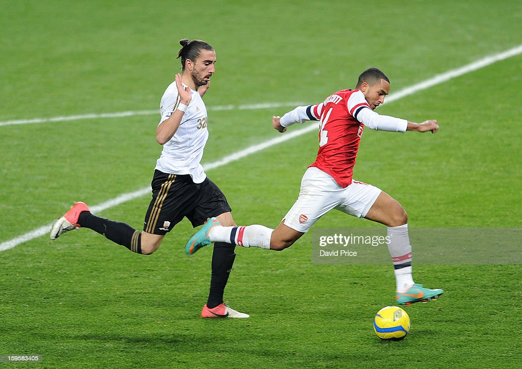 <a gi-track='captionPersonalityLinkClicked' href=/galleries/search?phrase=Theo+Walcott&family=editorial&specificpeople=451535 ng-click='$event.stopPropagation()'>Theo Walcott</a> of Arsenal is closed down by Chico Flores of Swansea during the FA Cup Third Round Replay match between Arsenal and Swansea City at the Emirates Stadium on January 16, 2013 in London, England.