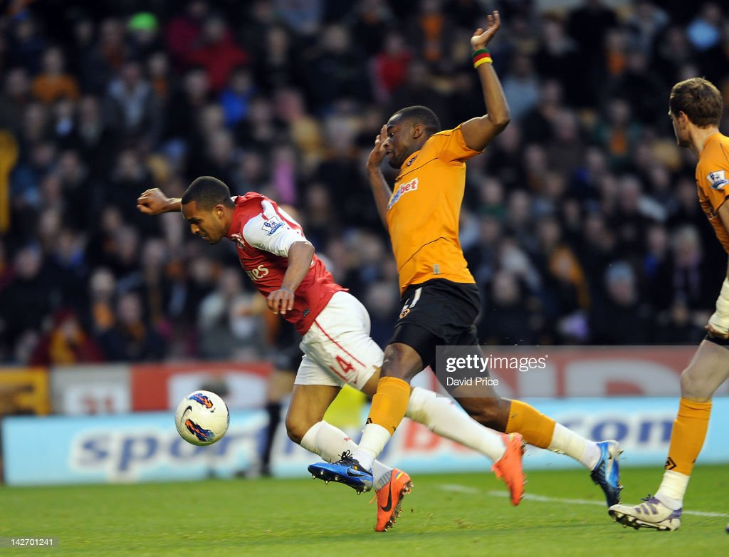 Theo Walcott of Arsenal is fouled by Sebastien Bassong of Wolves for a penalty to Arsenal during the Barclays Premier League match between...