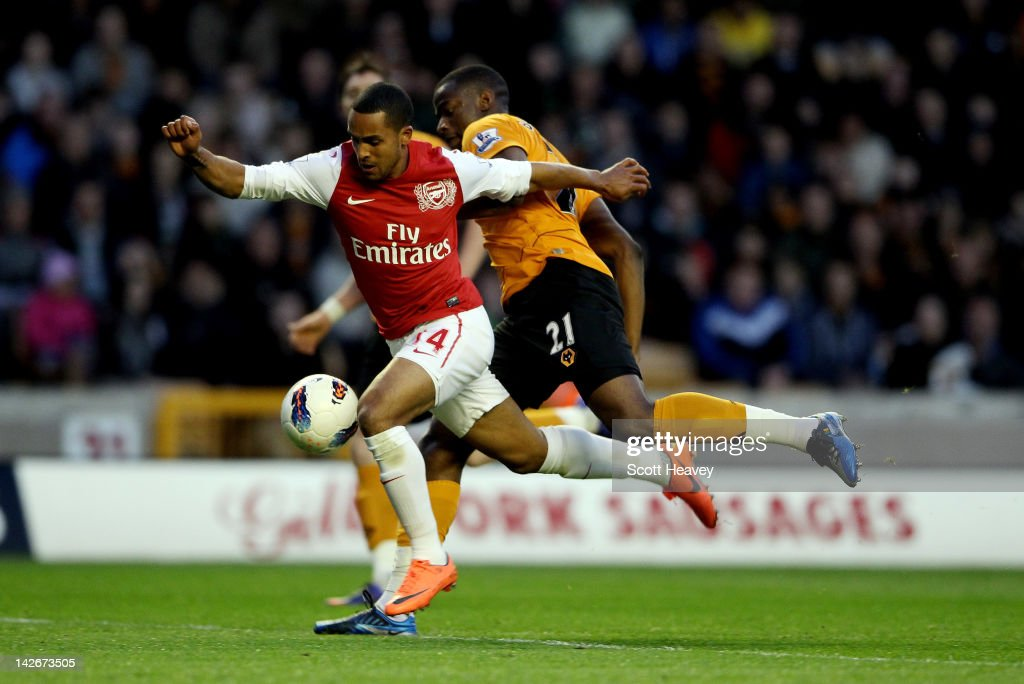 Theo Walcott of Arsenal is fouled by Sebastien Bassong of Wolves to earn a penalty during the Barclays Premier League match between Wolverhampton...