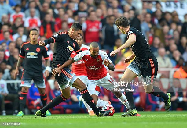 Theo Walcott of Arsenal is tackled by Chris Smalling of Manchester United during the Barclays Premier League match between Arsenal and Manchester...