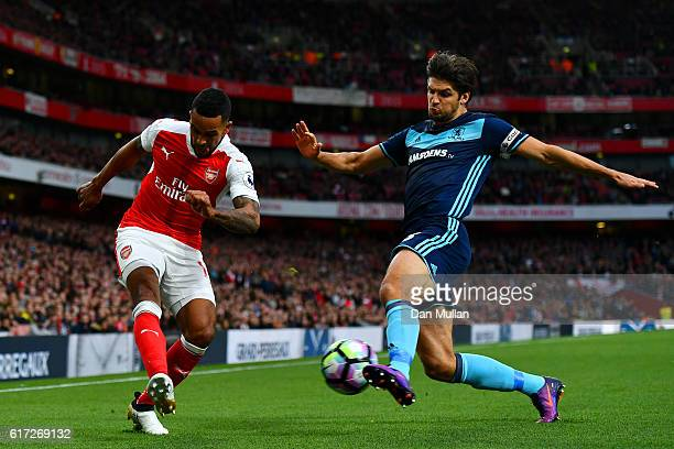 Theo Walcott of Arsenal is tackled by George Friend of Middlesbrough during the Premier League match between Arsenal and Middlesbrough at Emirates...