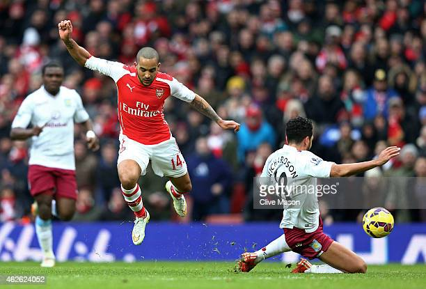 Theo Walcott of Arsenal is tackled by Kieran Richardson of Aston Villa during the Barclays Premier League match between Arsenal and Aston Villa at...