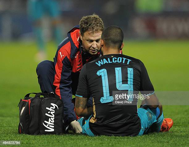 Theo Walcott of Arsenal is treated by Physio Colin Lewin during the Capital One Cup 4th Round match between Sheffield Wednesday and Arsenal at...