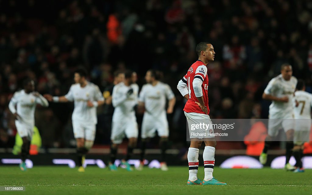 <a gi-track='captionPersonalityLinkClicked' href=/galleries/search?phrase=Theo+Walcott&family=editorial&specificpeople=451535 ng-click='$event.stopPropagation()'>Theo Walcott</a> of Arsenal looks dejected as Swansea celebrate their first goal during the Barclays Premier League match between Arsenal and Swansea City at the Emirates Stadium on December 1, 2012 in London, England.