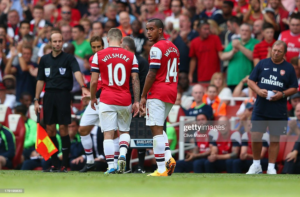 Theo Walcott of Arsenal looks on as team mate Jack Wilshere is substituted during the Barclays Premier League match between Arsenal and Tottenham Hotspur at Emirates Stadium on September 01, 2013 in London, England.