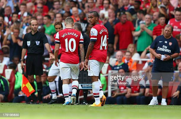 Theo Walcott of Arsenal looks on as team mate Jack Wilshere is substituted during the Barclays Premier League match between Arsenal and Tottenham...