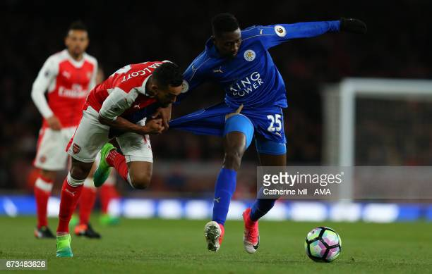 Theo Walcott of Arsenal pulls on the shorts of Wilfred Ndidi of Leicester City during the Premier League match between Arsenal and Leicester City at...