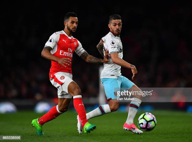 Theo Walcott of Arsenal puts pressure on Manuel Lanzini of West Ham United during the Premier League match between Arsenal and West Ham United at...
