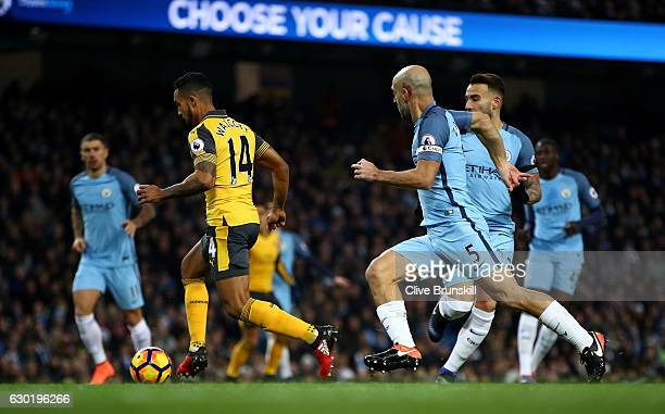 Theo Walcott of Arsenal runs through to scores his sides first goal during the Premier League match between Manchester City and Arsenal at the Etihad...