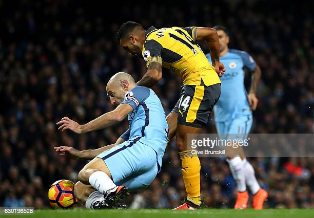 Theo Walcott of Arsenal scores his sides first goal during the Premier League match between Manchester City and Arsenal at the Etihad Stadium on...