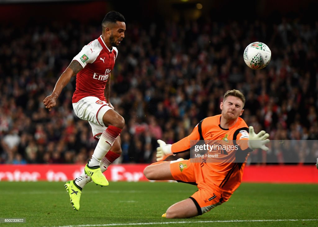 Theo Walcott of Arsenal scores his sides first goal past Ian Lawlor of Doncaster Rovers during the Carabao Cup Third Round match between Arsenal and Doncaster Rovers at Emirates Stadium on September 20, 2017 in London, England.