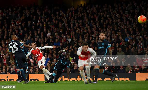 Theo Walcott of Arsenal scores his side's opening goal during the Barclays Premier League match between Arsenal and Manchester City at Emirates...