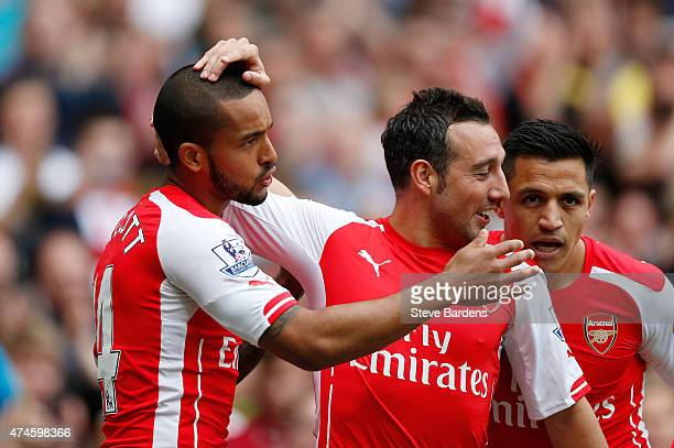 Theo Walcott of Arsenal scores his team's first goal with his team mates Santi Cazorla and Alexis Sanchez during the Barclays Premier League match...