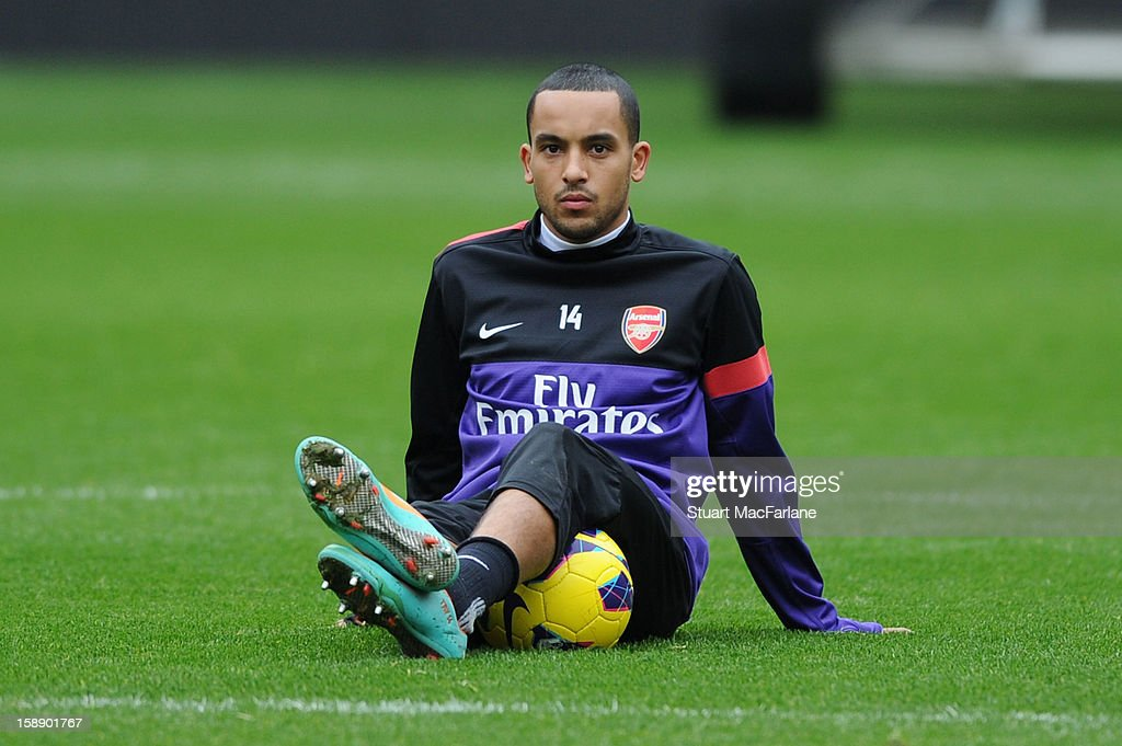 Theo Walcott of Arsenal sits on the pitch during a training session at Emirates Stadium on January 03, 2013 in London, England.