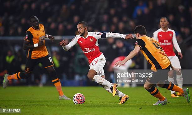 Theo Walcott of Arsenal takes on Alex Bruce of Hull City during the Emirates FA Cup Fifth Round Replay match between Hull City and Arsenal at KC...