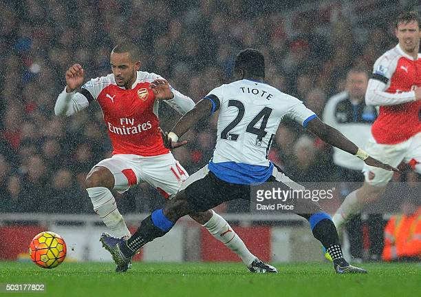 Theo Walcott of Arsenal takes on Cheick Tiote of Newcastle during the Barclays Premier League match between Arsenal and Newcastle United at Emirates...