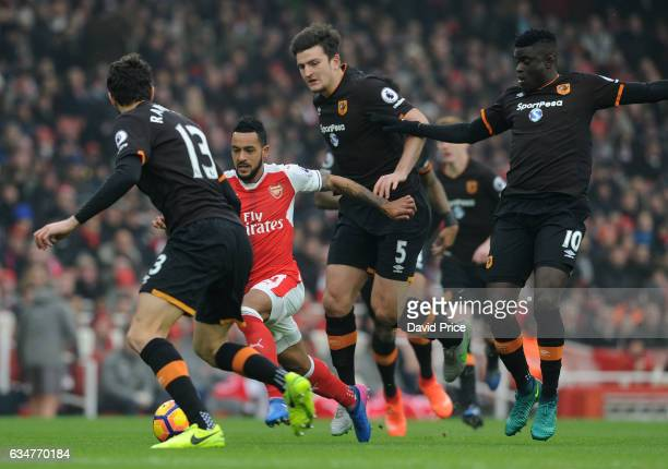 Theo Walcott of Arsenal takes on Harry Maguire Andrea Ranocchia and Alfred N'Diaye of Hull during the Premier League match between Arsenal and Hull...