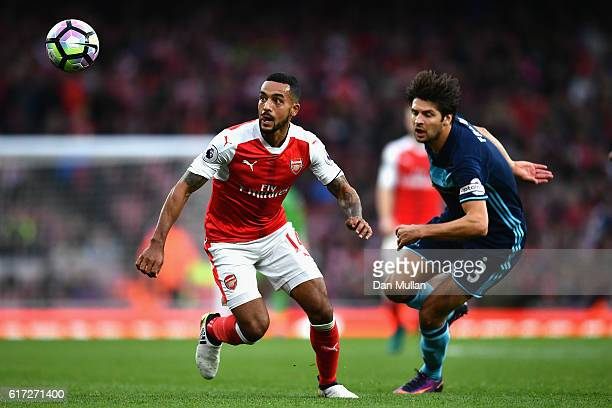 Theo Walcott of Arsenal watches the ball while George Friend of Middlesbrough attempts to chase him down during the Premier League match between...