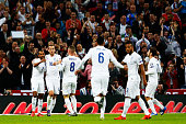 Theo Walcott of England celebrates with team mates after scoring during the UEFA EURO 2016 Group E qualifying match between England and Estonia at...