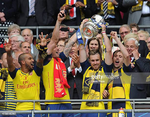 Theo Walcott Olivier Giroud Aaron Ramsey and Nacho Monreal with the FA Cup Trophy after the match between Arsenal and Aston Villa in the FA Cup Final...