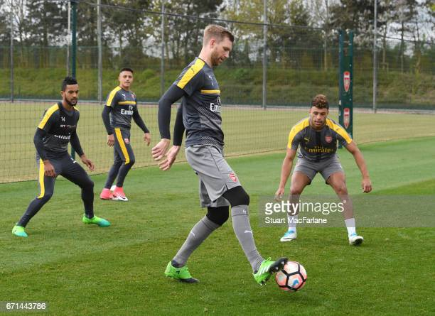 Theo Walcott Per Mertesacker and Alex OxladeChamberlain of Arsenal during a training session at London Colney on April 22 2017 in St Albans England