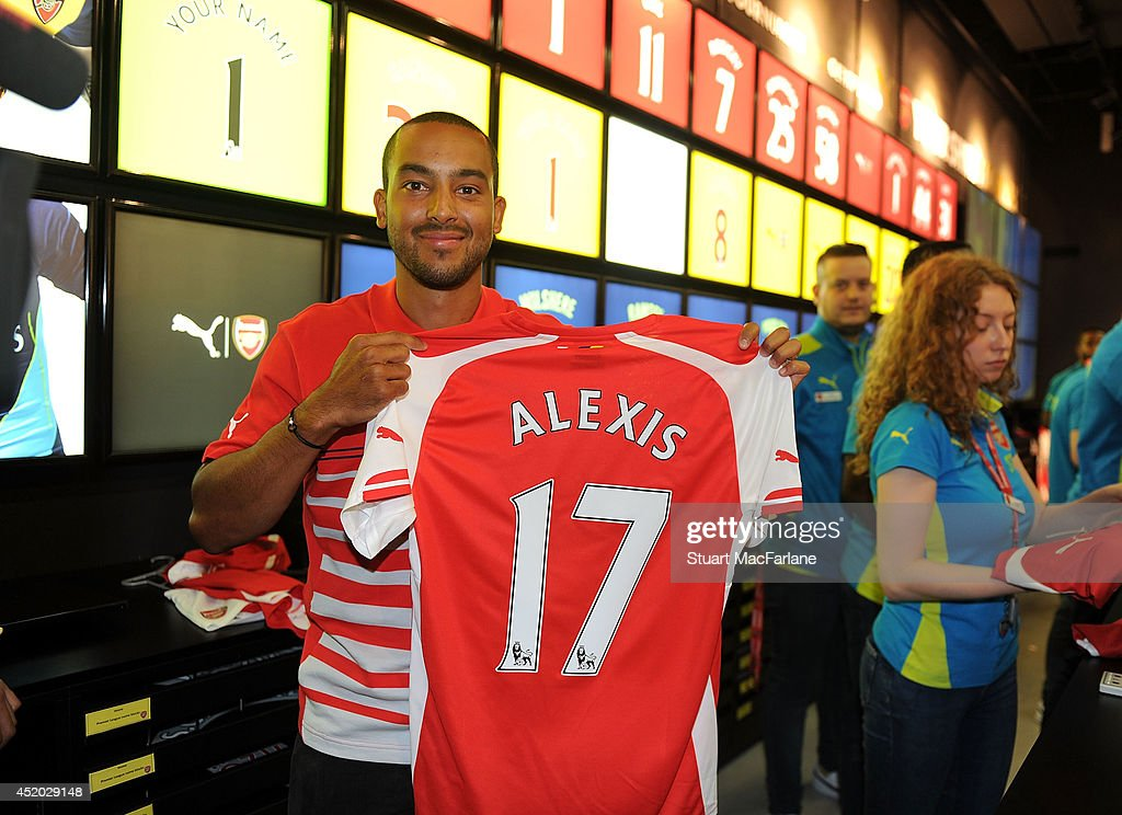 Theo Walcott prints new signing Alexis Sanchez home shirt in the Armoury store at Emirates stadium on July 11, 2014 in London, England.