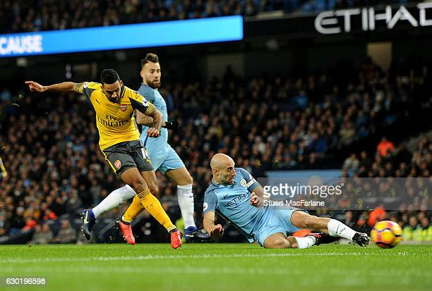 Theo Walcott shoots past Man City captain Pablo Zabaleta to score for Arsenal during the Premier League match between Manchester City and Arsenal at...
