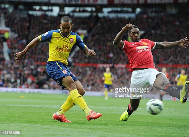 Theo Walcott shoots past Man United defender Tyler Blackett to score the Arsenal goal during the Barclays Premier League match between Manchester...