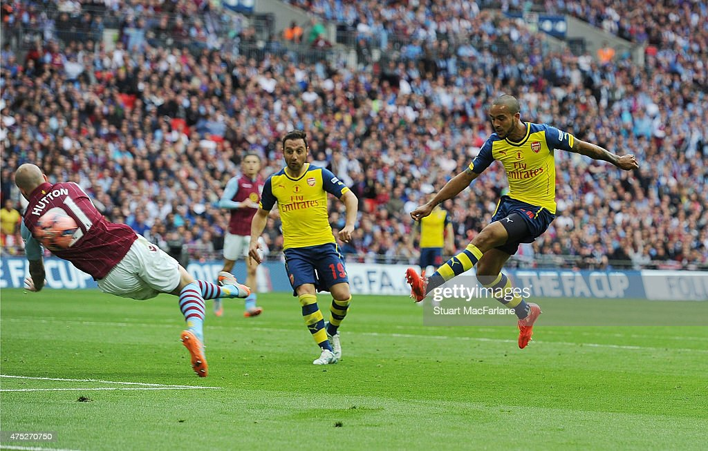 <a gi-track='captionPersonalityLinkClicked' href=/galleries/search?phrase=Theo+Walcott&family=editorial&specificpeople=451535 ng-click='$event.stopPropagation()'>Theo Walcott</a> shoots pastAston Villa defender <a gi-track='captionPersonalityLinkClicked' href=/galleries/search?phrase=Alan+Hutton&family=editorial&specificpeople=839355 ng-click='$event.stopPropagation()'>Alan Hutton</a> to score for Arsenal during the FA Cup Final between Aston Villa and Arsenal at Wembley Stadium on May 30, 2015 in London, England.