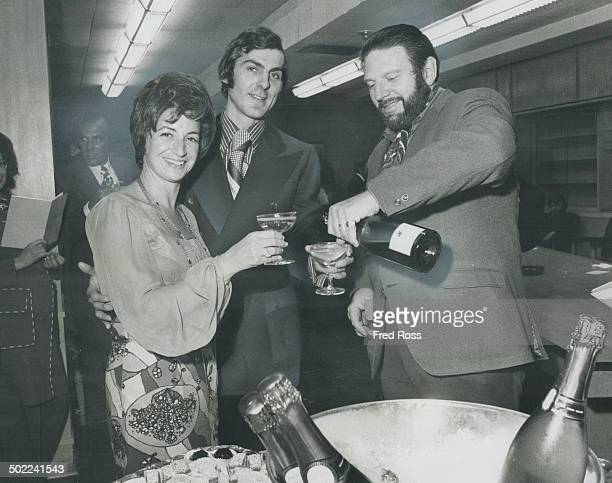 Theodore Bikel the Israeli singeractor pours champagne for Mrs Henry Shanoff and Paul Rothstein at a reception after his concert in the Beth Tzedec...