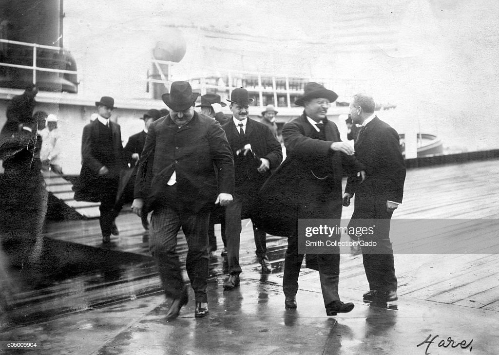 Theodore Roosevelt at Ellis Island, disembarking from a ship on a rainy day and walking with a small crowd, with a cheerful facial expression, September 16, 1903. From the New York Public Library. (Photo by Smith Collection/Gado/Getty Images).