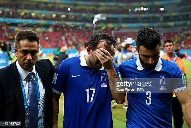 Theofanis Gekas and Giorgos Tzavellas of Greece walk off the pitch after the defeat in the 2014 FIFA World Cup Brazil Round of 16 match between Costa...