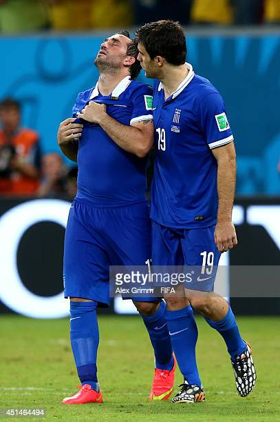 Theofanis Gekas of Greece walks off the pitch with Sokratis Papastathopoulos after the defeat in the 2014 FIFA World Cup Brazil Round of 16 match...